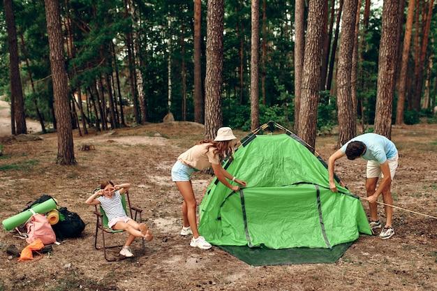 Счастливая семья на выходных в сосновом лесу. папа и мама ставят палатку, а их дочь сидит и веселится. походы, отдых, походы.