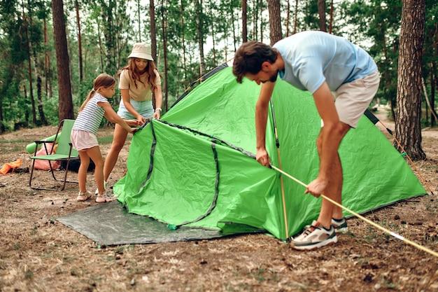 Счастливая семья на выходных в сосновом лесу вместе поставила палатку. ребенок-девочка помогает родителям разбить лагерь. походы, отдых, походы.