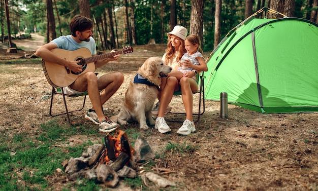 週末に松林で幸せな家族が一緒にテントを張った。両親がキャンプを設定するのを手伝っている子供の女の子。キャンプ、レクリエーション、ハイキング。