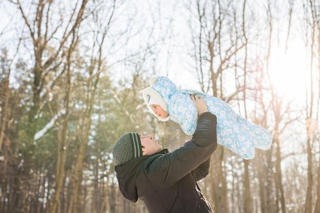 Счастливая семья на зимней прогулке на природе. папа вырвало мальчика.