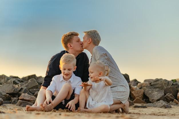 Счастливая семья на пляже беременная мама, сын и дочь