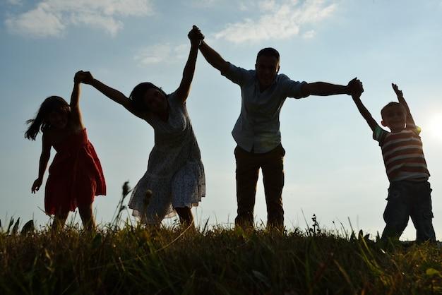 幸せな時間を持つ美しい夏の牧草地の幸せな家族