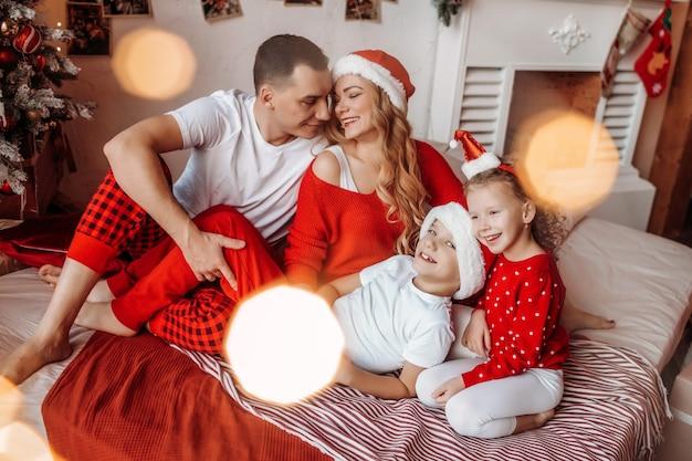 새해와 메리 크리스마스를 기다리는 침대에 행복한 가족