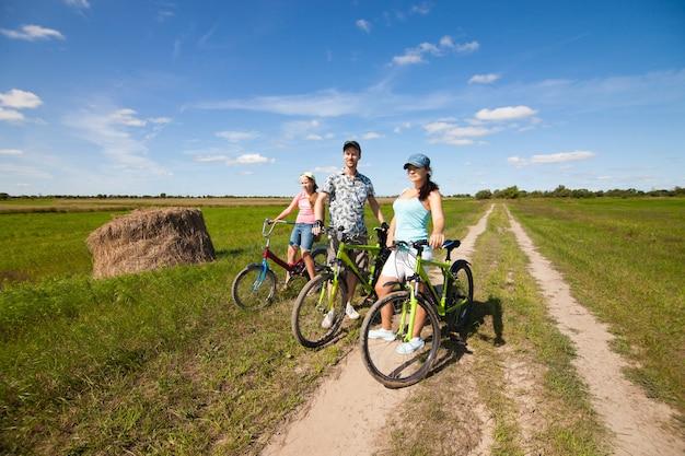 여름에 들판에 서 있는 자전거를 타고 행복한 가족