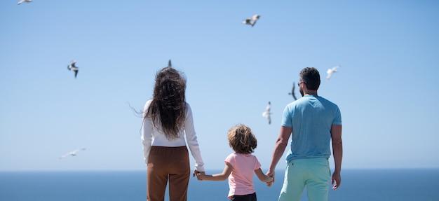青い海で夏休みの父母と子を楽しんでいるビーチの人々の幸せな家族...