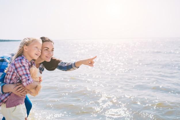 해변에서 행복한 가족. 여름 방학에 재미 사람들. 엄마와 아이가 푸른 바다와 하늘을 배경으로. 휴가 여행 컨셉