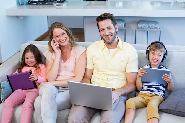 Счастливая семья на диване вместе с помощью устройств