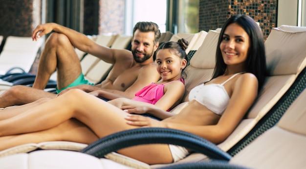 リゾートの幸せな家族。ハンサムな父親、美しい母親、そして彼らの小さなかわいい娘は、プール付きの大きなスパセンターのサンラウンジャーに横たわっています。休暇でリラックス