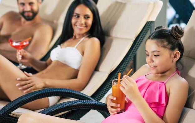 リゾートの幸せな家族。ハンサムな父、美しい母、そして彼らの小さなかわいい娘は、プールと飲み物のジュースとカクテルのある大きなスパセンターのサンラウンジャーに横たわっています