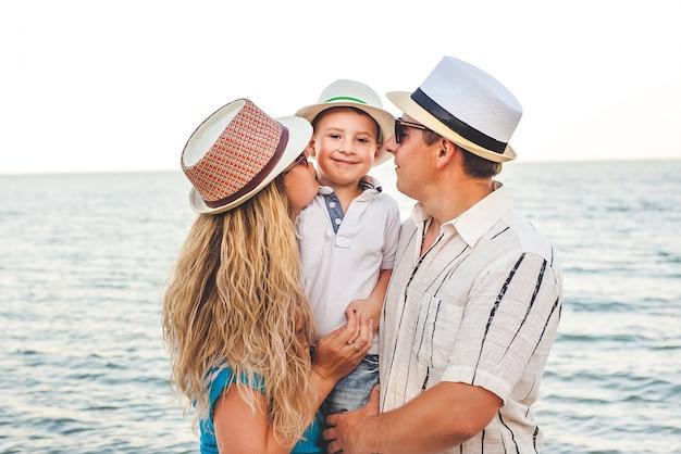 休暇で幸せな家族。ママ、パパ、幼い息子がビーチに立っています。