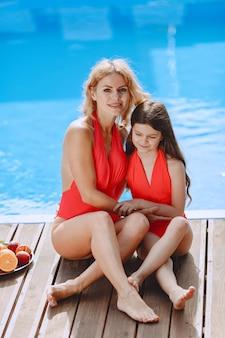 休暇中の幸せな家族。プールのそばに座っている水着の母と娘。