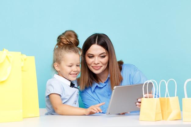 幸せな家族のオンラインショッピングの概念。孤立したインターネットで物事を覆っているママと子供。