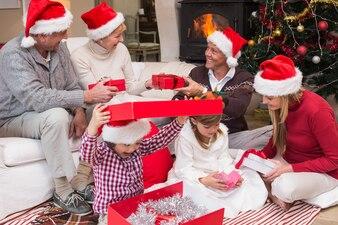 リビングルームで一緒に家庭でクリスマスプレゼントを開く幸せな家族