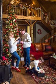 Счастливая семья, открывая подарочную коробку на рождество