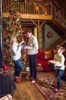 Счастливая семья открывает подарочную коробку Premium Фотографии