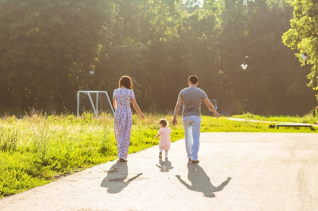 Happy family outdoor activity. rear view of parents and baby daughter having fun and walking in
