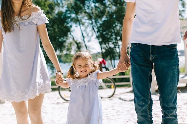 一緒に時間を過ごす幸せな家族。父、母、娘が楽しいし、ビーチで走っている