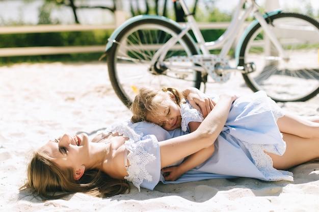 一緒に時間を過ごす幸せな家族。父、母、娘は楽しいし、ビーチで遊ぶ