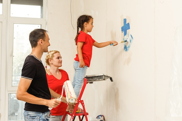 Happy family painting a wall at home