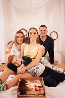 Happy family in pajamas on the bed