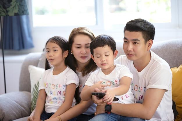 息子と娘がソファーに座って、家族で一緒に遊んで幸せな家族親