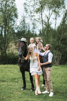 Happy family, parents and children, enjoying the horse presence