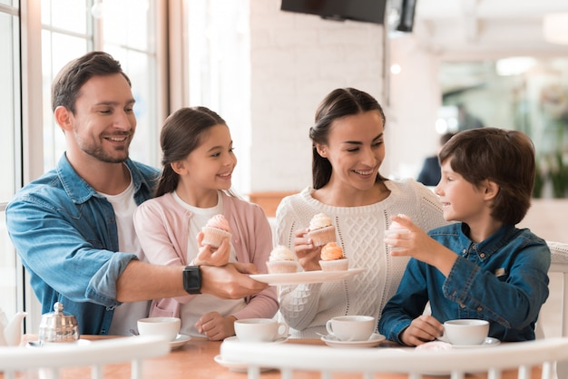 Happy family parents and kids share cakes in cafe.