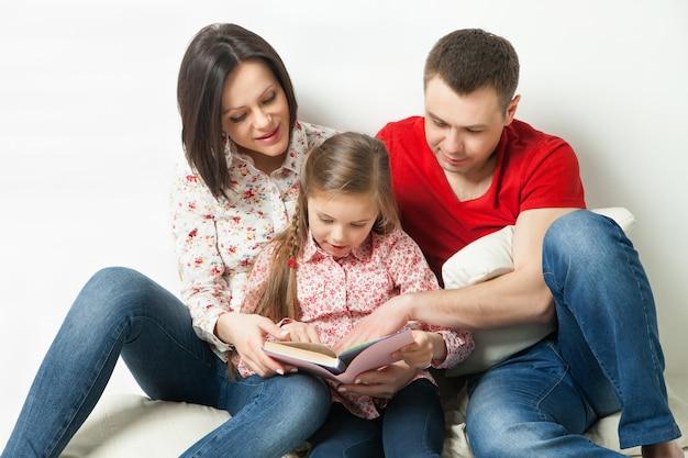 Счастливая семья. родители читают книгу с дочерью на белом фоне