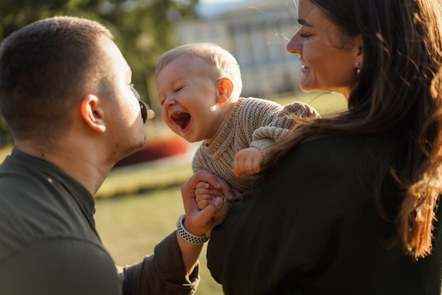 Happy family in a park. dad is holding dummy in mouth. mother holding baby son trying to take out a pacifier. high quality photo