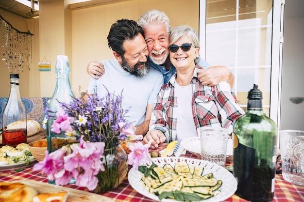 友情と幸福で一緒に祝う準備ができている食べ物や飲み物でいっぱいのテーブルの前で抱き締めて楽しんでいる高齢者の肖像画の幸せな家族