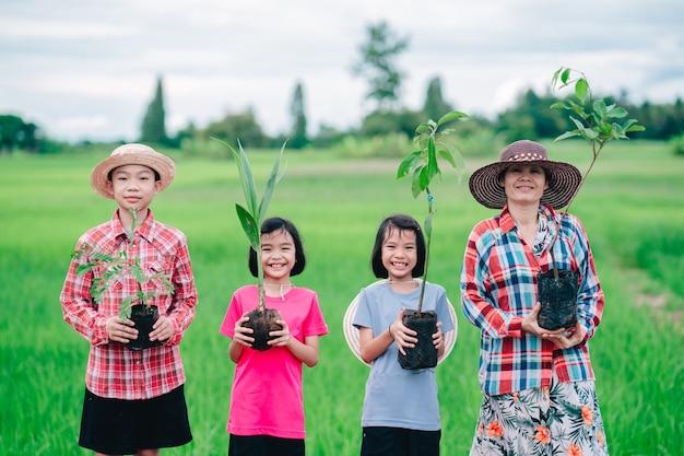 Счастливые семейные люди держат посев дерева для посадки в сад на органическом зеленом рисовом поле