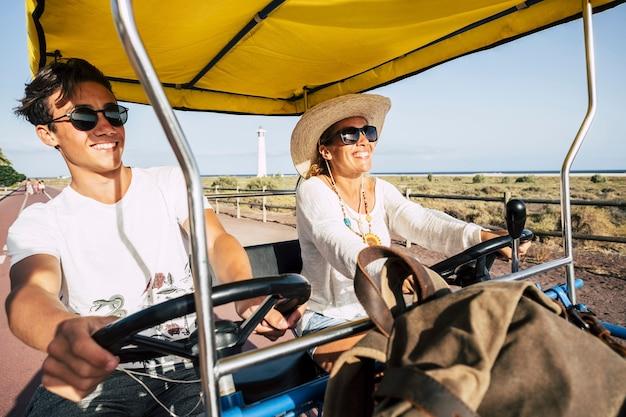 屋外のレジャー活動を楽しんで、一緒にたくさん笑っている珍しい面白い自転車を持つ幸せな家族の人々-休暇に乗っている幸せな母と息子のためのビーチと海