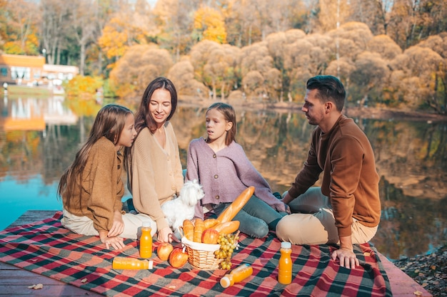 Happy family on a picnic in the park at autumn