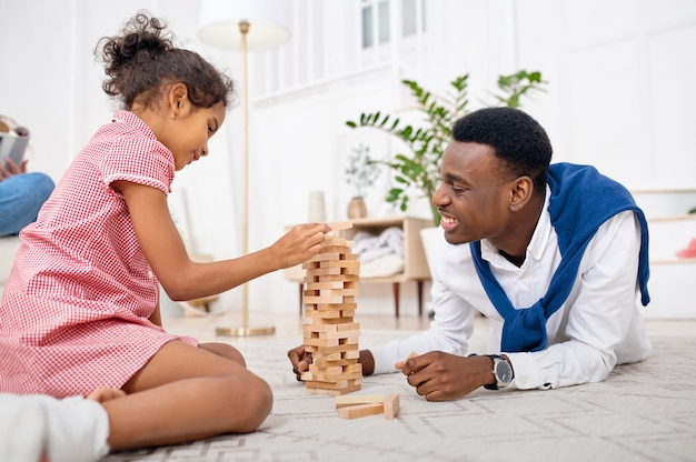 Happy family play game in living room. mother, father and their little daughter poses at home together, good relationship. mom, dad and female child, photo shoot in house