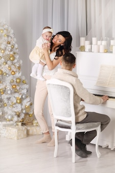 Happy family play the piano and dance around the christmas tree