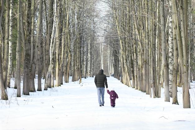 행복한 가족은 야외에서 눈 속에서 놀고 웃고 있습니다. 도시 공원 겨울 날입니다.