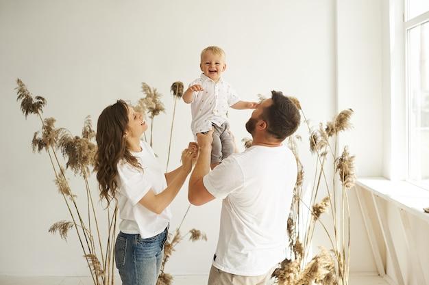 갈대와 흰색 배경에 자녀와 함께 집에서 놀고 행복한 가족