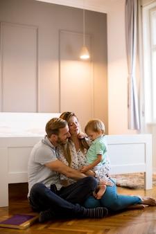 寝室の床で遊んで幸せな家族