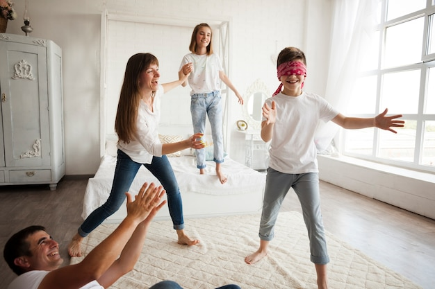 Счастливая семья, играющая любителя слепого дома