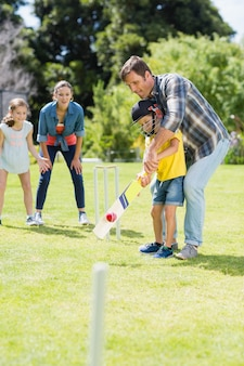 Happy family playing cricket together