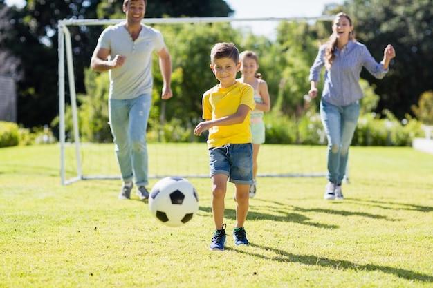 公園でサッカーをして幸せな家族