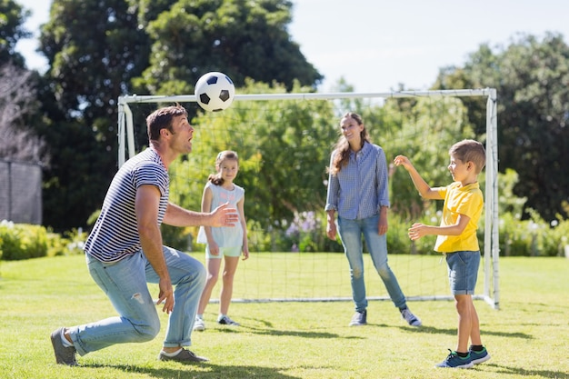 Happy family playing football in the park