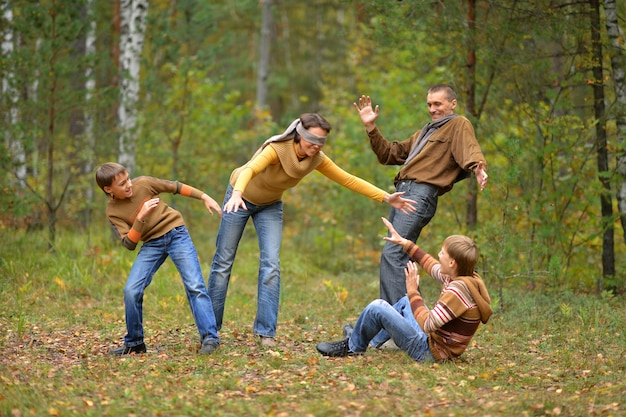 Happy family playing hide and seek in autumn forest