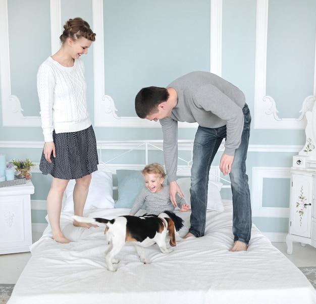 寝室の自由な日に遊ぶ幸せな家族。教育の概念