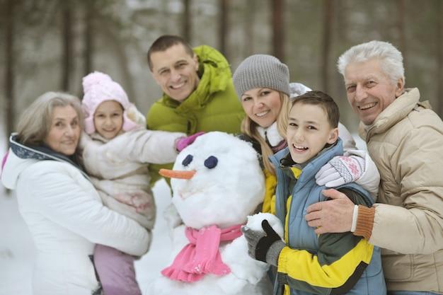自然の中で屋外の美しい晴れた冬の日に新雪で遊んで雪だるまを構築する幸せな家族