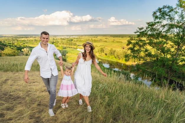 牧草地の新鮮な空気で遊んで幸せな家族 Premium写真