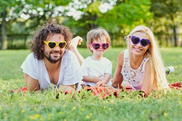 公園で遊んで幸せな家族。母、父、息子は夏、春に自然の中で一緒に遊びます。