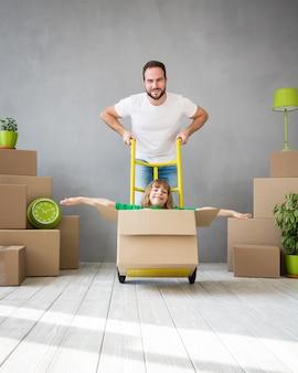 一緒に家の日を移動して楽しんでいる新しい家の父と子に遊んで幸せな家族