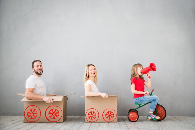 一緒に家を引っ越して楽しんでいる新しい家の父母と子に遊んで幸せな家族