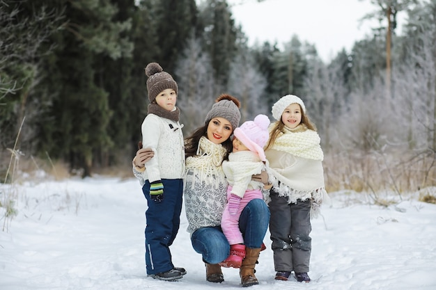 Happy family playing and laughing in winter outdoors in snow. city park winter day.